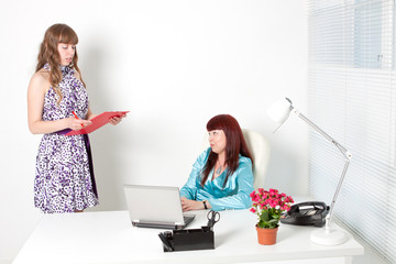 Confident business woman and a young secretary in a office