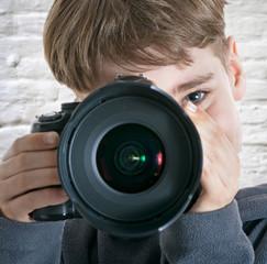 Junge fokussiert mit der Kamera im Studio
