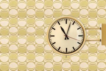 Seventies vintage office clock against a retro wallpaper back
