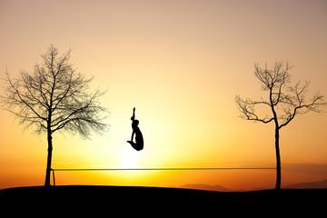 silhouette of girl jumping on slackline in sunset