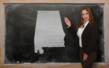 Teacher showing map of alabama on blackboard