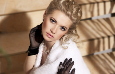 Beautiful woman on ladder in fur and evening dress in hotel