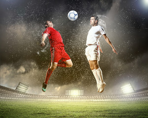 Poster de jardin Le football two football players striking the ball