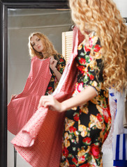 Woman shopping dresses looking in mirror