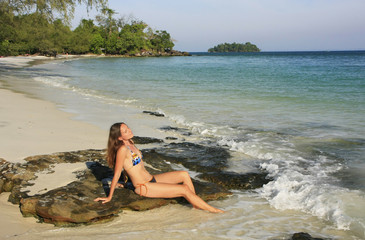 Young woman sitting on a beach of Koh Rong island, Cambodia