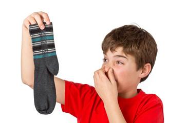 Junge mit stinkenden Socken hält sich die Nase zu