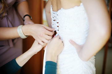 female hands helping the bride to dress