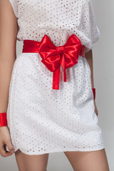 Red bow on a white dress on the grey background