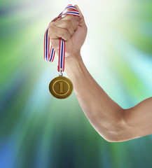 hand and gold medal