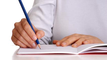 Manos escribiendo sobre un cuaderno.