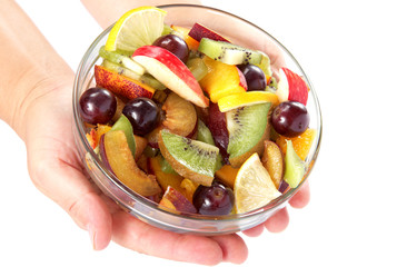 Women's hands holding bowl with fresh fruits salad on white back