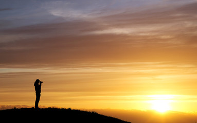 silhouette of photographer in sunset