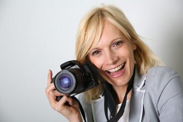 Cheerful woman photographer holding camera