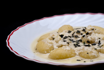 italian gnocchi with four cheese sauce isolated on black