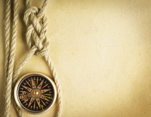 Rope and compass on the old paper background