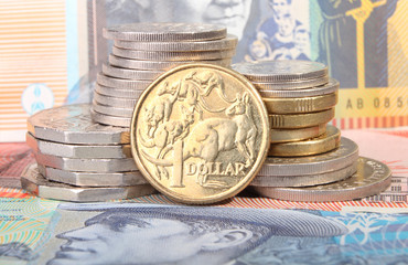 Australian dollar coin on currency background