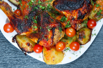 Roasted chicken with fried potatoes and cherry tomatoes.