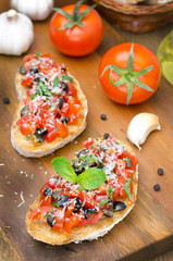 Italian bruschetta with tomato, olives, basil and cheese