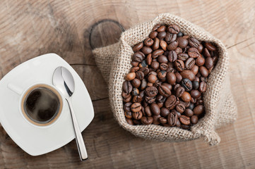coffee beans in jute bag with cup of coffee