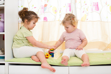 two kids sisters play together indoors