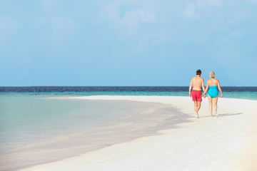 Rear View Of Senior Romantic Couple Walking In Tropical Sea