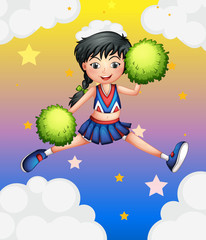 A cheerleader jumping with her green pompoms