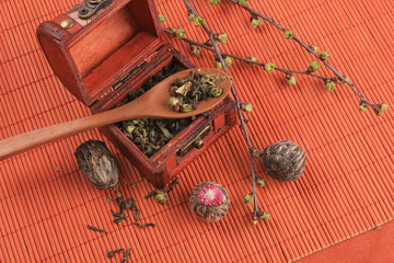 tea chest with dry lotus flowers on an orange background