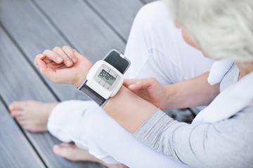 grauhaarige Frau misst idealen Blutdruck