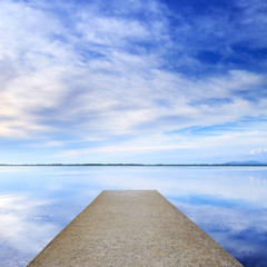 Concrete pier or jetty and on a blue lake and sky reflection