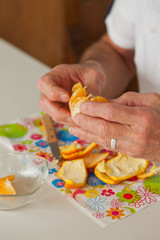 Closeup of hands of senior man peeling fresh orange.
