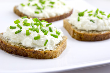 Fototapeta brown bread with curd cheese and chives obraz