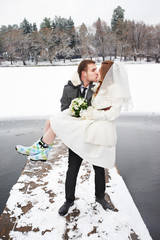 Kiss bride and groom on walk in winter