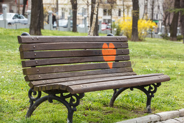 Wooden park bench at a park with  red heart painted on it.