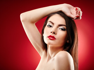 Beautiful glamour brunette on red background