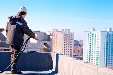Roofer installing roofing felt by means of gas blowpipe torch