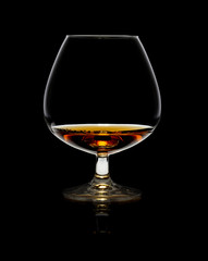 Glass of whiskey over black background