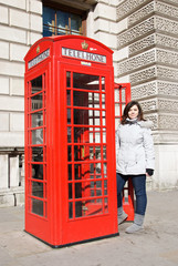 Girl close to a red english telephone-box