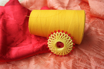 Closeup picture of yellow threads on colorful cloths