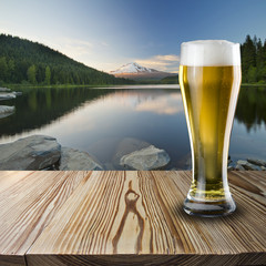 Glass of beer on wood table with mountain scene