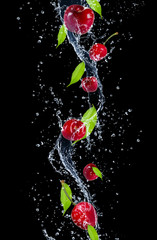 Deurstickers Opspattend water Cherries in water splash, isolated on black background