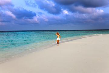 The sporting woman runs on the seashore. Maldives