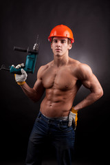 Muscular worker with an electric drill on a black background.