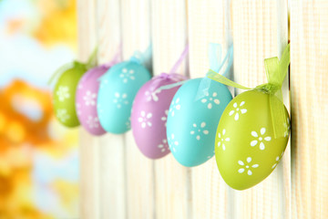 Art Easter background with eggs hanging on fence