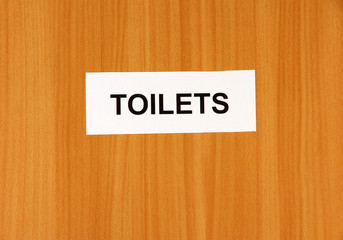 Toilet sign on wooden background