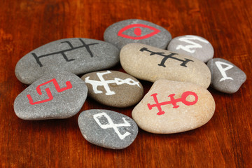Fortune telling  with symbols on stones on wooden background