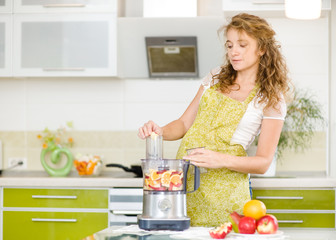 pregnant woman using a juicer, standing in the kitchen