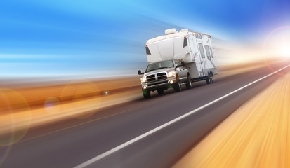 Truck pulling fifth wheel camping trailer.