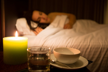 Woman relaxing in bed (dish focus)