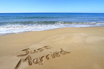 """""""Just married"""" written on golden sandy beach"""