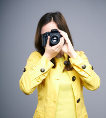 Attractive young woman in a yellow jacket. Woman photographer co
